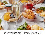 Small photo of Glass of champagne close-up on the table with different breakfast and brunch dishes like croissants, eggs benedict, coffee and fruits. Selective focus