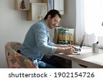 Small photo of At domestic workplace. Pensive young man engaged in distant learning remote studying prepare for exam at home. Diligent student make notes from online tutorial correct mistakes in written paper work