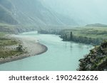 Beautiful misty mountain landscape with wide mountain river. Dark green gloomy scenery with big mountain river in mist. Dark atmospheric view to great river among big mountains in rainy weather.