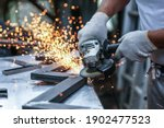 Small photo of the hands of the master saw the metal with a grinder. metal works in the workshop close up