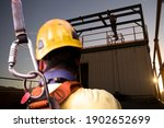 Small photo of Safety workplace construction worker wearing yellow safety helmet fall arrest PPE harness attached an inertia reel shock absorber device on harness defocused workmate using standing working background