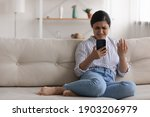 Small photo of Confused angry indian woman sit on couch at home read spam message on phone screen have problem with correct work. Shocked mad mixed race lady web store client deal with scam online. Copy space