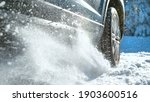 Small photo of LOW ANGLE, CLOSE UP, DOF: Fresh snow flies up from a large vehicle's spinning wheel. Car's wheels spin and spew up pieces of snow and snowflakes as it attempts to gain traction on the slippery road.