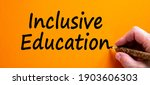 Small photo of Inclusive education symbol. Hand writing 'inclusive education', isolated on orange background. Business, inclusion and inclusive education concept. Copy space.