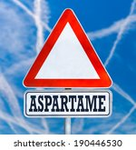 Small photo of Conceptual image of a triangular white traffic warning sign with the word - Aspartame - a non-saccharide articifial sweetener which has long been debated over safety concerns, blue sky with contrails.