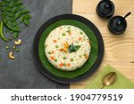 Small photo of Upma made of samolina or rava upma, most famous south indian breakfast item which is arranged in a black plate and garnished with fried cashew nut and curry leaves with grey colour background.