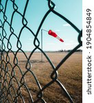 Small photo of A red flag blowing in the wind at an airport runway. Through wire fence in portrait outside perimeter of airport at the border. Windy weather through mesh fence by airport security with wind flag.
