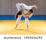 Small photo of Adult male judoka throwing young female judo girl with hip throw