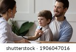 Small photo of Caring woman doctor hold stethoscope listen to happy small boy patient heart chest in hospital. Young father with little son child do checkup examination at pediatrician in clinic. Healthcare concept.