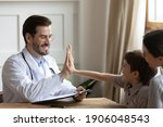 Small photo of Happy young Caucasian male doctor give high five to cute small 7s boy patient at consultation with mom in hospital. Smiling pediatrician make deal cheer little kid child in clinic. Healthcare concept.