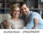 Small photo of Head shot portrait of smiling young caucasian man embracing affectionate older senior mother in glasses, enjoying sweet tender time indoor, spending weekend leisure together, family relations concept.