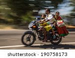 Small photo of KERALA, INDIA - FEBRUARY 17: Young family riding on a bike (blurred motion). Motorbike is the most favorite vehicle and most affordable for India.