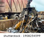 Small photo of Loading scrap metal into a truck Crane grabber loading metal rusty scrap in the dock A grapple truck loads scrap industrial metal for recycling