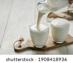 Small photo of Pouring homemade kefir, buttermilk or yogurt with probiotics. Yogurt flowing from glass bottle on white wooden background. Probiotic cold fermented dairy drink. Trendy food and drink. Copy space left
