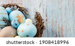 Small photo of Banner.Easter eggs, feathers in a nest on a blue wooden background. The minimal concept of Easter. Top view. An Easter card with a copy of the place for the text.