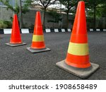 Small photo of A row of traffic cones on the road. These objects are temporary traffic control devices for directing and avoiding sections of the road being repaired or diverting traffic.