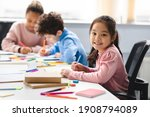 Small photo of Academic Concept. Smiling junior asian school girl sitting at desk in classroom, writing in notebook, posing and looking at camera. Group of diverse classmates studying in the background