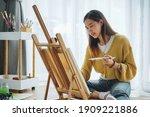 Female artist painting on...