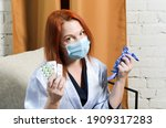 Small photo of Young red-haired woman in medical mask holds pills and rubber gloves in her hands. Concept: quarantined coronavirus treatment, illness, outpatient treatment, medications.