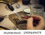 Small photo of Heating. Close up hands of jeweller, goldsmiths making of silver ring with gemstone using professional tools. Craft production, precious and luxury jewel, hand made occupation. Workshop, artwork.