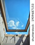 Small photo of open roof window, skylight. A wide-open window of a full skylight looks inward, seeing the sky isolated