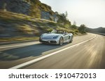 Small photo of California, USA - January 10, 2021: A silver Porsche Boxster 25 Years Roadster is driven on The mountain road by sea