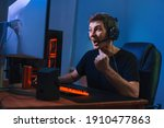 Small photo of Young caucasian pro gamer win in online video game, feels happy and exited, show YES hand gesture. Professional cyber sportsman playing tournaments on computer with headphones at home, red and blue