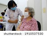 Small photo of Sao Paulo, SP, Brazil - February 5, 2021: A nurse gives a shot of COVID-19 CoronaVac vaccine to an elderly woman during a priority vaccination program for people with more than 90 years old.