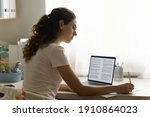 Small photo of Confident female interpreter translate document from foreign language to english use pc app make notes in paper copy. Professional young woman editor correct errors mistakes in printed article text