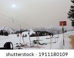 Small photo of Grusch Danusa, Switzerland - 2.6.2021: Sky filled with orange tinged Sahara sand with the Sun peeking through high on a mountain in the Swiss Alps. Many skis and poles in the foreground in the snow.