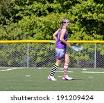 A young Lacrosse player on the field during a game. - stock photo