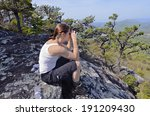 A woman hiker on a rock overlook using her binoculars.  Cell phone on her pocket. - stock photo