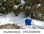 A Blue Snow Shovel Leaning...
