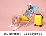Small photo of Full length smiling young traveler tourist man in hat sit on deck chair using mobile cell phone typing sms message isolated on pink background. Passenger travel on weekend. Air flight journey concept