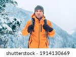 Man dressed bright orange softshell jacket with backpack have trekking on the winter mountains route. Active people or survival in the nature concept image.