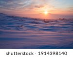 Winter arctic landscape. Satellite dishes in the winter snow-covered tundra in the Arctic. Sunset over the tundra and mountains. Cold frosty winter weather. Chukotka, Siberia, Far North of Russia.