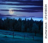 autumn landscape. fence on the hillside meadow near forest in mountain at night in moon light - stock photo