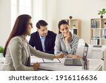 Small photo of Happy future house buyers meeting real estate agent. Professional realtor talking to clients and offering flats options on computer. Smiling couple consulting bank worker or loan broker at her office