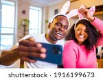 Small photo of Young african american man and woman wearing cute easter bunny ears in the house taking selfie on smartphone