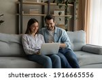 Small photo of Happy husband wife newlyweds rest on sofa hold laptop choose furniture for new home buy consumer goods online. Young family couple using pc discuss flat renovation options planning trip on vacation
