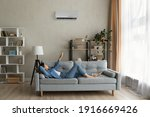 Small photo of Glad millennial female buyer of air conditioner relax on sofa hold controller breath cool fresh air despite of hot summer day outside. Happy young lady regulate climate at home using modern ac device