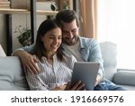Small photo of Fond memories. Smiling spouses hug on sofa recall sweet moments of life to mind watch wedding video on electronic pad. Young couple in love browse online travel agencies websites plan honeymoon trip
