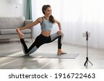 Small photo of Positive sporty lady stretching in front of smartphone at home, copy space. Beautiful young woman fitness blogger shooting video for her followers or having personal training online