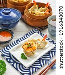 Small photo of Mentai Shumai or Mentai Dim Sum and Jiaozi. Two of the dim sum variants. Served on white ceramic plate, on white background.