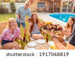 Small photo of Group of cheerful young friends gathered around the table, drinking beer and having fun at backyard poolside barbecue party while the host is serving food