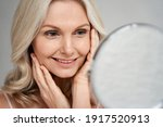 Small photo of Happy 50s middle aged woman model touching face skin looking in mirror. Smiling mature older lady pampering, enjoying healthy skin care, aging beauty, skincare treatment cosmetic products concept.