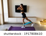 Small photo of Home workout with resistance band. Girl training at home. Sports woman exercising with resistance band. Strong sporty girl in sportswear. Fitness exercise. Girl watching online tutorials on tablet.
