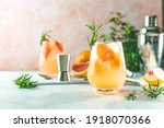 Small photo of Tequila cocktail or cold lemonade with grapefruit juice, tinted with the aroma of a fresh sprig of rosemary on fashion pastel pink background.