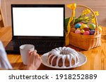 Small photo of A laptop with a blank screen on a table festively decorated for the Easter holiday. Adorned working place with flowers and a basket, with colorful eggs and cake.