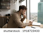 Small photo of Information to think about. Pensive male look at cell ponder on job offer received by email. Young businessman sit by large window at modern kitchen, read important message on phone screen